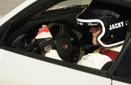 Jacky Ickx, avec le modèle Superfast Power Control, au volant d'une Porsche.