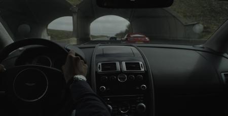 Photo de l'intérieur d'une Aston Martin et d'une Jaeger Lecoultre sur le poignet du conducteur