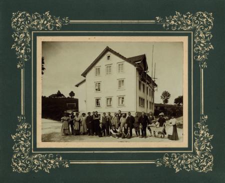 Georges-Édouard Piaget, des membres de la famille et des artisans devant la fabrique installée dans l'ancien Café Français en 1911. ©Fonds privés